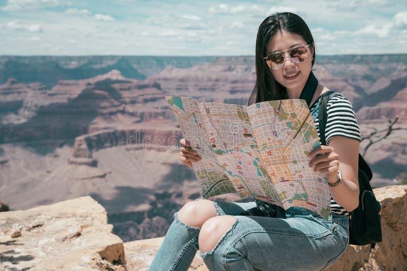 拿着纸地图的女孩搜寻路线 免版税库存照片