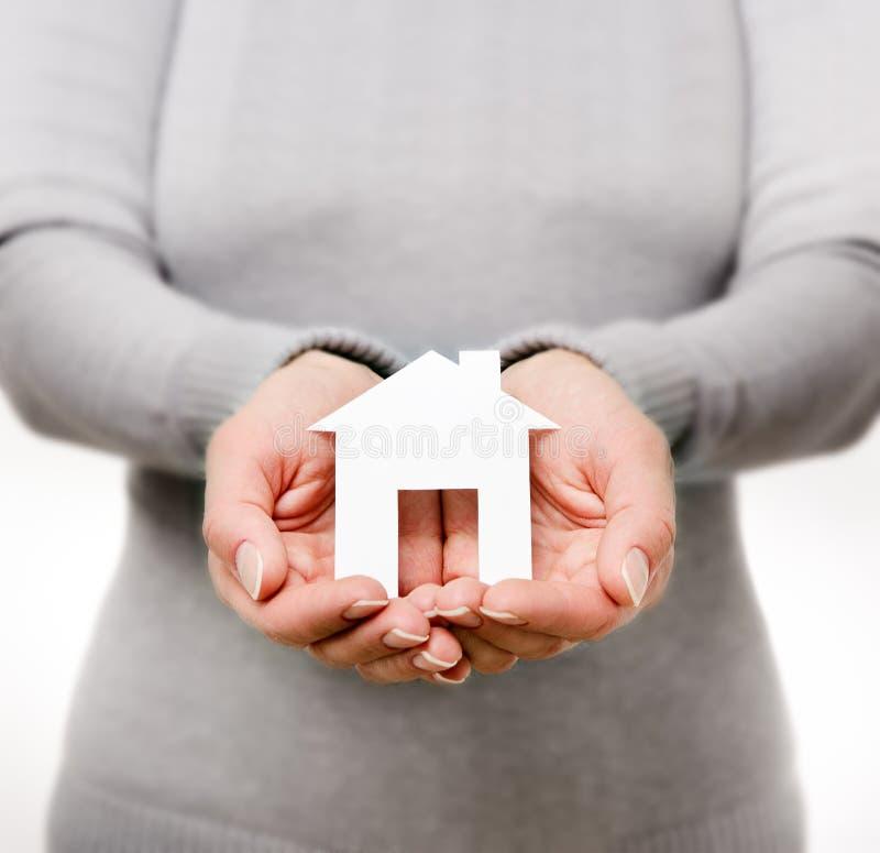拿着纸房子的手 免版税库存图片