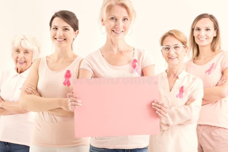 拿着纸板料的小组妇女 免版税库存照片