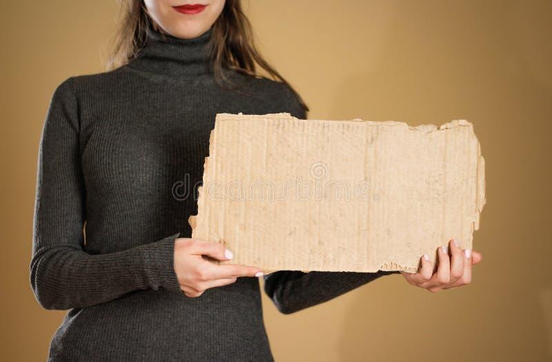拿着纸板的片断一件灰色夹克的一个女孩 预习功课 免版税图库摄影