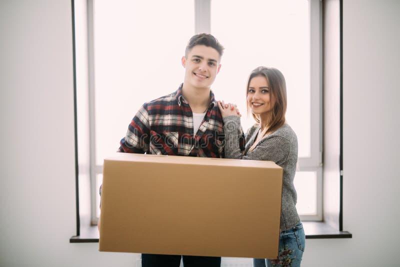 拿着纸板箱和搬到新的地方的年轻愉快的夫妇 免版税图库摄影