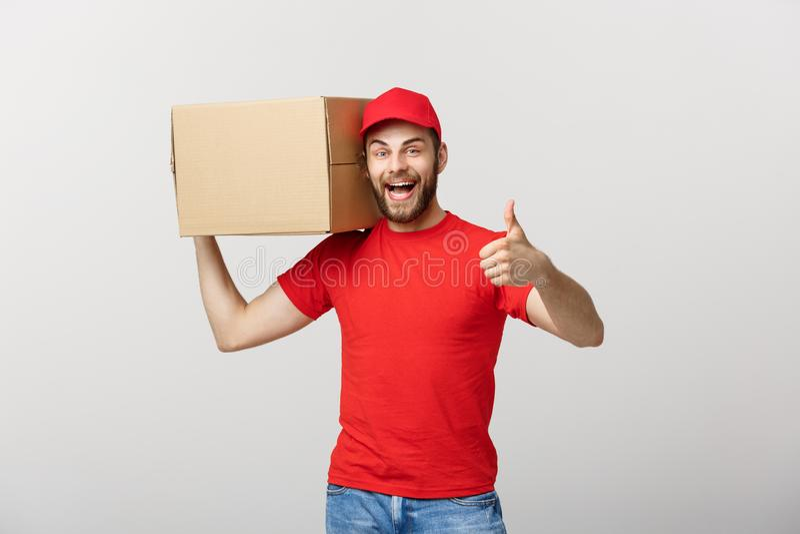 拿着纸板箱和显示他的赞许的快乐的年轻英俊的送货人,当站立反对灰色时 免版税图库摄影