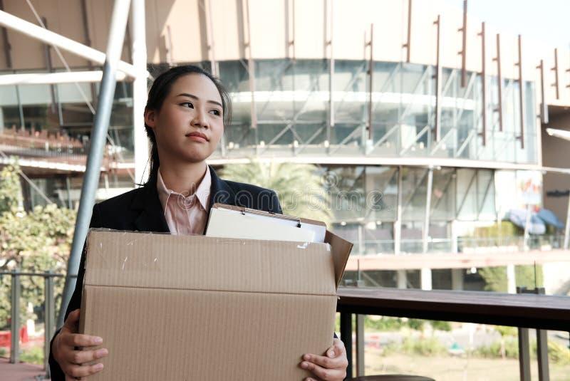 拿着纸板箱的沮丧的妇女包含个人belon 免版税库存照片