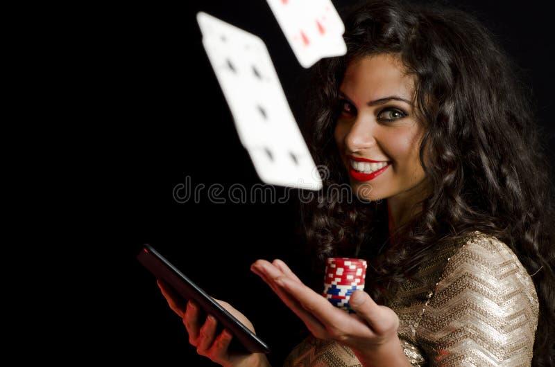 拿着纸牌筹码和片剂,黑背景的女孩 免版税库存图片