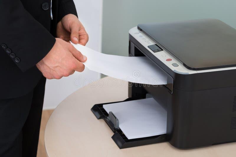 拿着纸的商人,当使用影印机时 库存照片