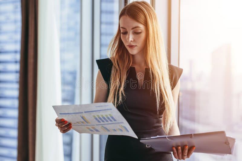 拿着纸的女性金融分析员学习站立反对窗口的文件有城市视图 免版税库存图片