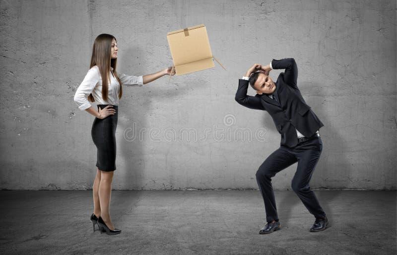 拿着纸盒箱子的具体背景的女实业家对一个蜷缩的人 免版税库存图片