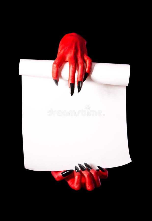 拿着纸纸卷的红魔手 免版税库存照片