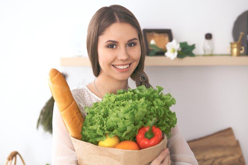 拿着纸袋的年轻愉快的妇女有很多蔬菜和水果,当微笑时 女孩做了购物并且准备为 图库摄影
