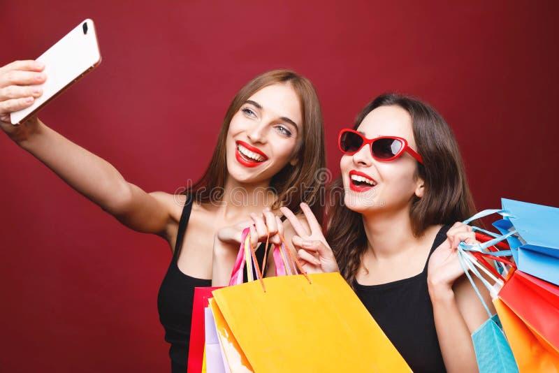 拿着纸购物袋和做Selfie的两个女朋友 图库摄影