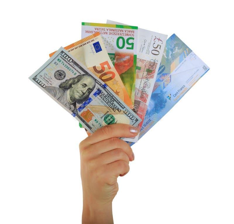 拿着纸钞票美元、欧元、瑞士法郎和英磅的女性手 库存照片