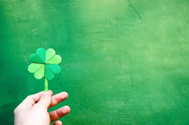 拿着纸origami绿色三叶草的手图片
