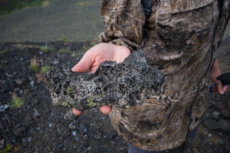 拿着结冰的火山的熔岩石头,特写镜头的妇女远足者的手 免版税图库摄影