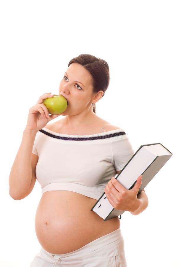 拿着绿皮书和苹果的孕妇 库存照片