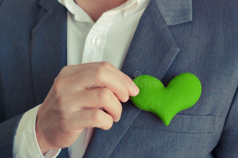 拿着绿色心脏的商人 免版税库存照片