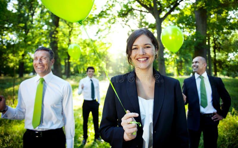 拿着绿色气球的商人在森林里 库存图片
