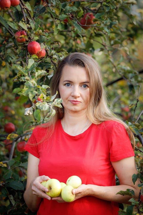 拿着绿色苹果的红色T恤杉的中间年迈的妇女在庭院里 免版税库存照片