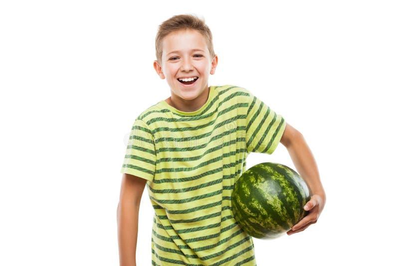 拿着绿色西瓜果子的英俊的微笑的儿童男孩 库存图片