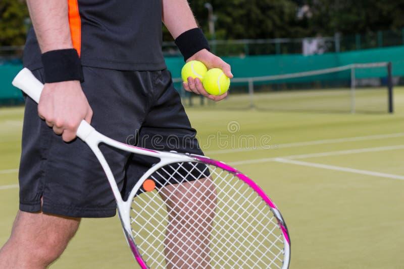 拿着网球和球拍的人特写镜头 免版税库存照片