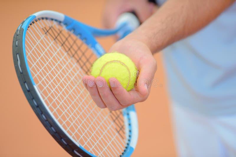 拿着网球拍和球的特写镜头手保持平衡服务 库存照片