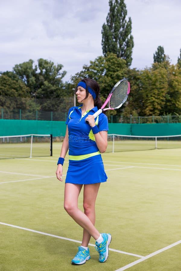 拿着网球拍o的体育衣物的美丽的少妇 库存照片