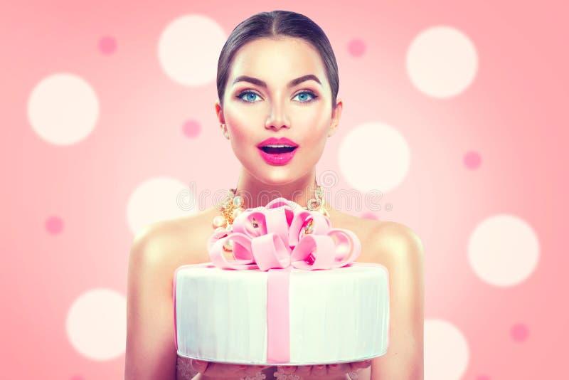 拿着美丽的党或生日蛋糕的时装模特儿女孩 免版税库存照片