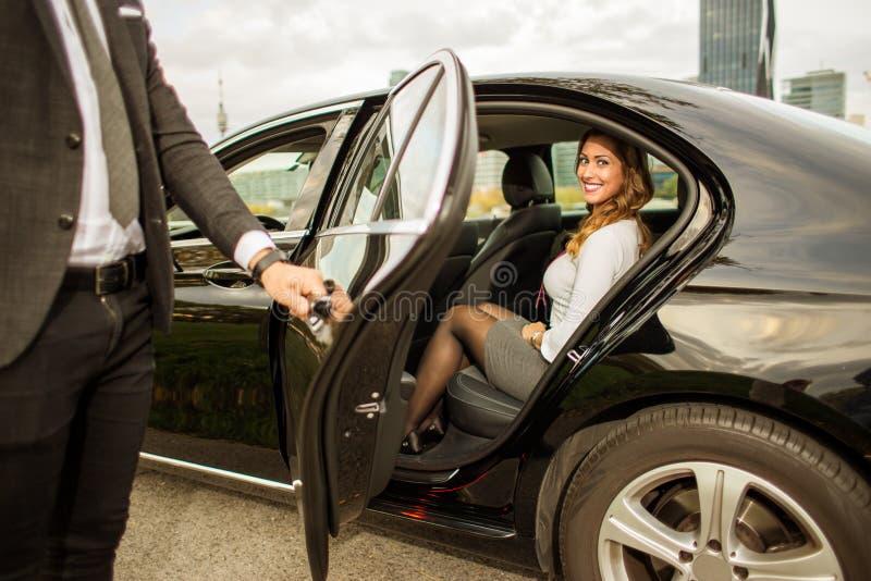 拿着美丽的女实业家的英俊的人车门 库存图片