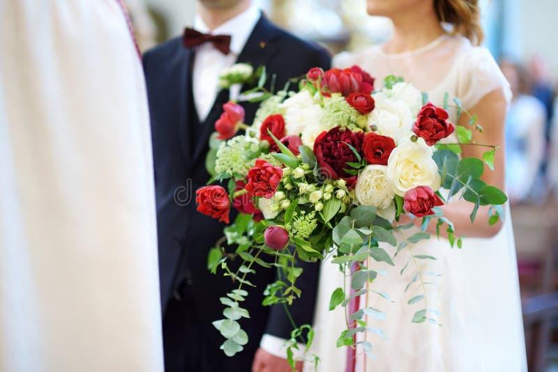 拿着美丽的婚礼花束的新娘在婚礼期间在教会里 免版税图库摄影