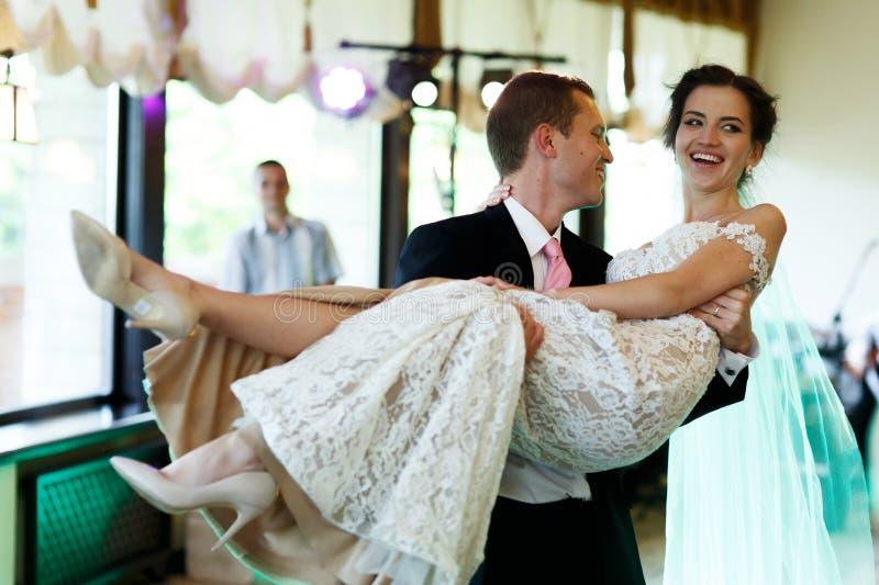 拿着美丽的性深色的新娘的英俊的坚强的新郎  免版税库存照片