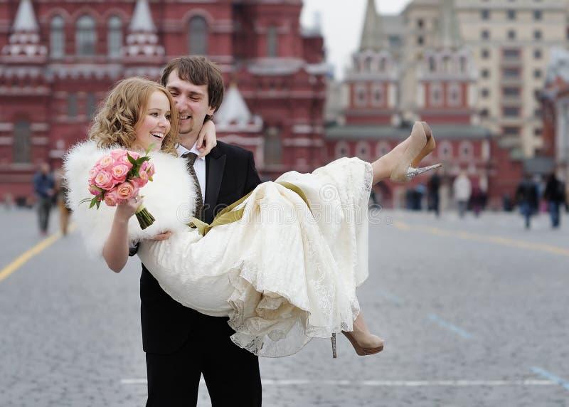 拿着美丽的新娘的愉快的新郎 库存图片