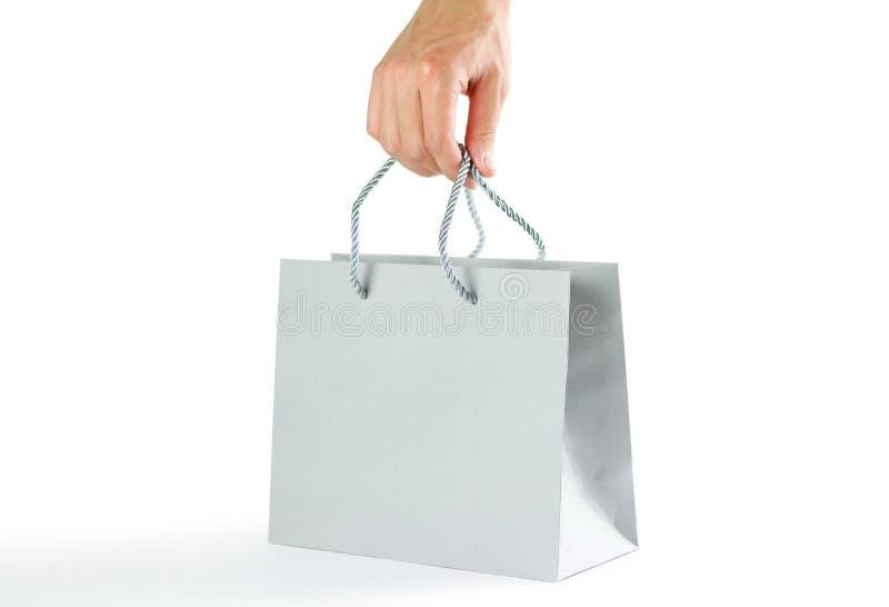 拿着美丽的礼物灰色袋子的手 关闭 背景查出的白色 库存图片