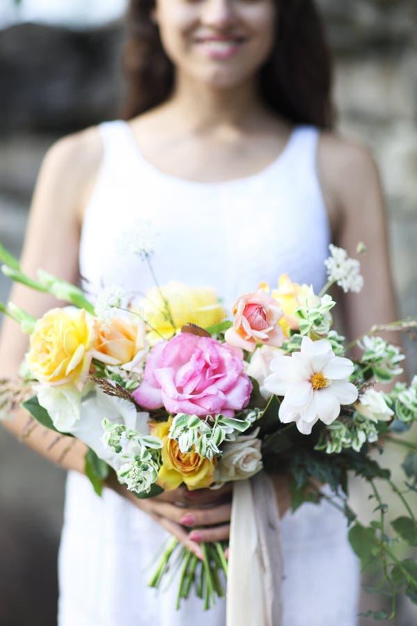拿着美丽的花束的白色婚礼礼服的年轻新娘 免版税库存图片