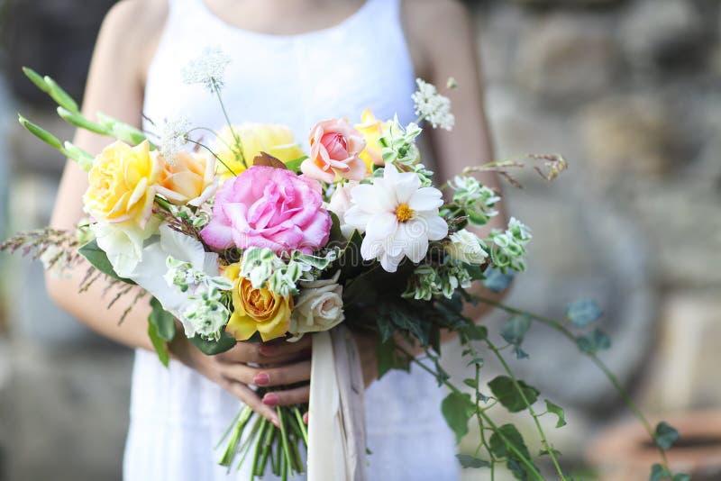 拿着美丽的花束的白色婚礼礼服的年轻新娘 库存照片