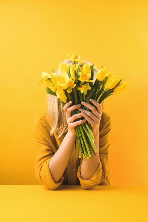 拿着美丽的黄色郁金香和黄水仙在黄色的妇女 免版税图库摄影