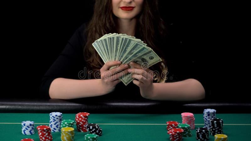 拿着美元束的愉快的妇女,坐在赌博娱乐场桌上,比赛优胜者,成功 库存照片