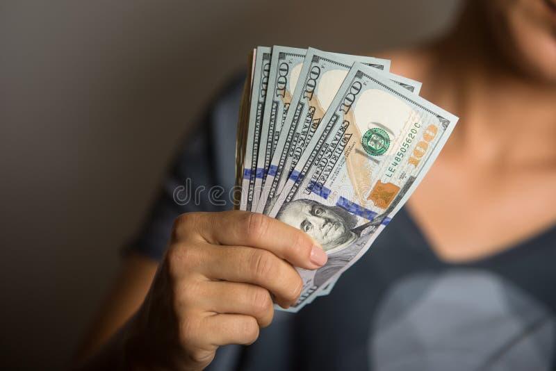 拿着美元的笔记妇女 库存图片