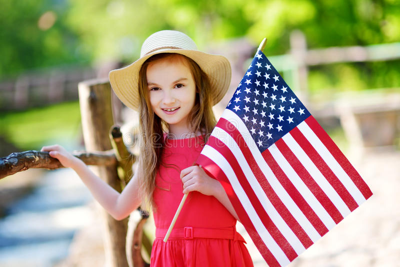 拿着美国国旗的可爱的小女孩佩带的帽子户外在美好的夏日 免版税图库摄影