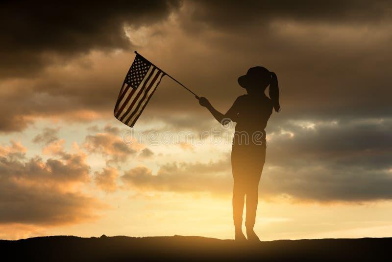 拿着美国国旗的女孩在日落 免版税库存照片