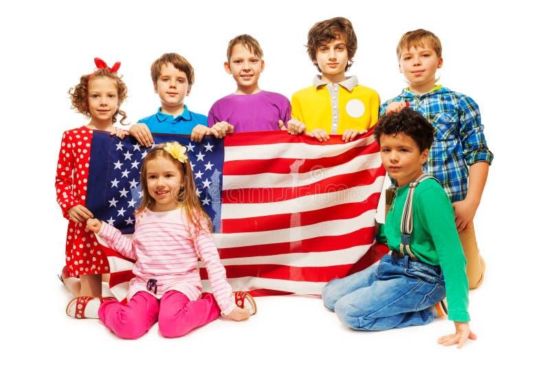拿着美国国旗的小组七个孩子 免版税库存照片