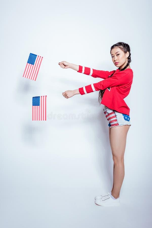 拿着美国国旗的爱国成套装备的美丽的亚裔女孩被隔绝在白色 库存照片