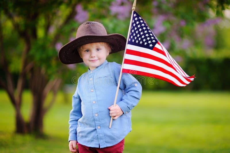 拿着美国国旗的逗人喜爱的小孩男孩在美丽的公园 免版税库存图片