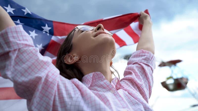 拿着美国国旗的骄傲的妇女、星条旗、自由和独立 免版税库存图片
