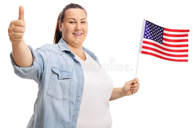 拿着美国旗子和放弃thums的肥头大耳的妇女 库存照片
