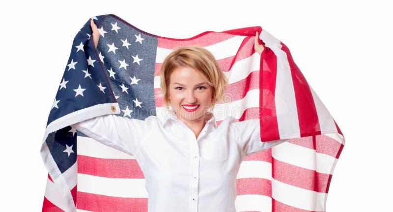 拿着美国旗子的微笑的爱国的妇女 美国庆祝7月4日 免版税图库摄影