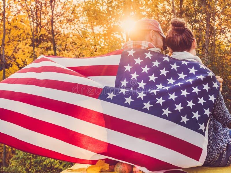 拿着美国旗子的愉快的已婚夫妇 免版税库存照片