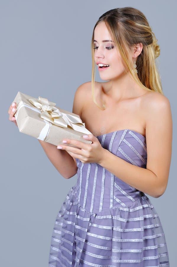 拿着美妙地被包裹的当前箱子的妇女 库存图片