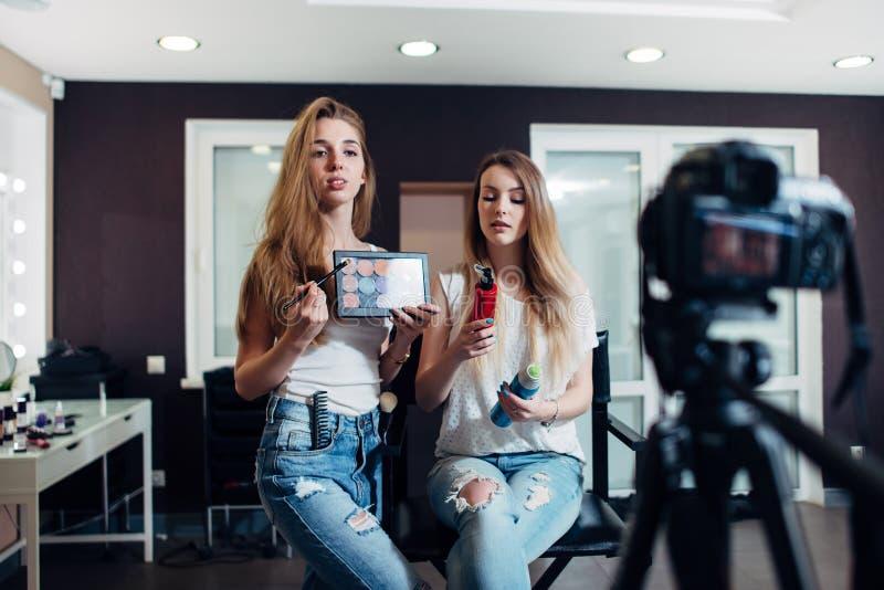 拿着美容品的少妇做录影在videoblog的化妆用品 免版税库存照片
