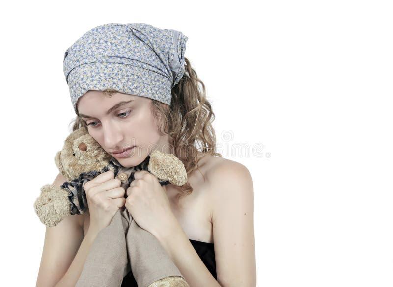 拿着老哀伤的玩具的女孩 免版税库存照片