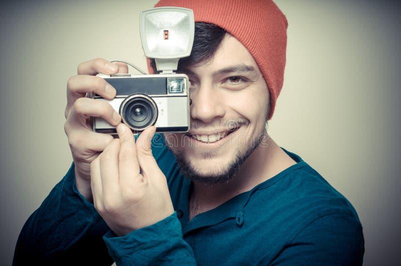 拿着老照相机的年轻时髦的人 免版税库存照片