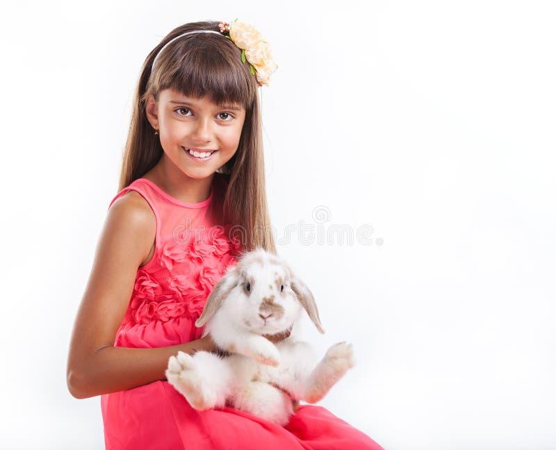 拿着耳朵下垂的兔子的女孩反对白色 库存图片